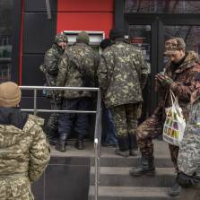 Ukrainian troops queue to withdraw hryvnia cash from an automated teller machine in Artemivsk, Ukraine, on Feb. 20, 2015 | Photo: Vincent Mundy, Bloomberg