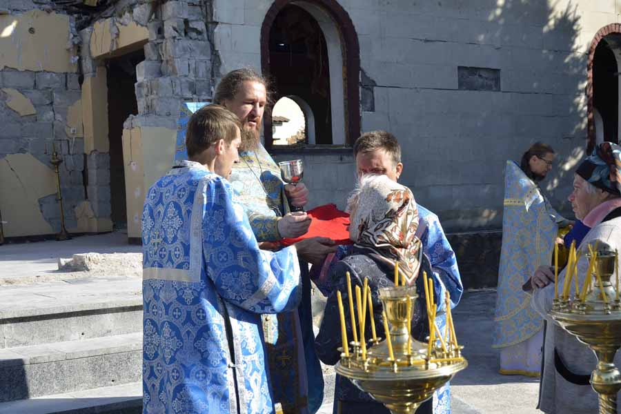 A parishioner receives communion among the ruins of her church