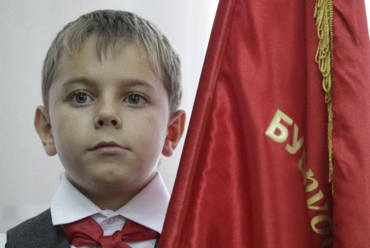 A boy, holding a flag and wearing red neckerchief, a symbol of the Pioneer Organization, attends a ceremony for the inauguration.