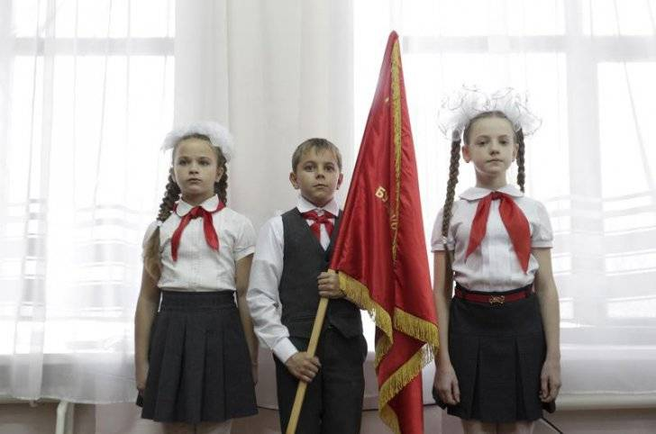 Children, wearing red neckerchiefs, a symbol of the Pioneer Organization, attend a ceremony for the inauguration.