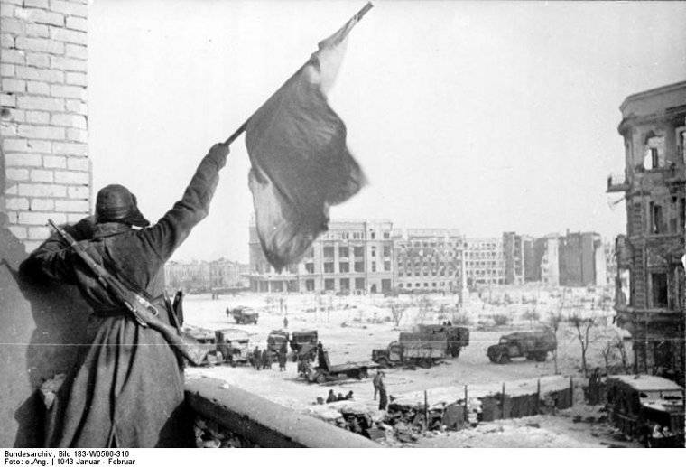 Ever defiant, a Soviet soldier waving a red flag at a building off the central square in Stalingrad, Russia, Jan-Feb 1943 (Georgi Zelma)