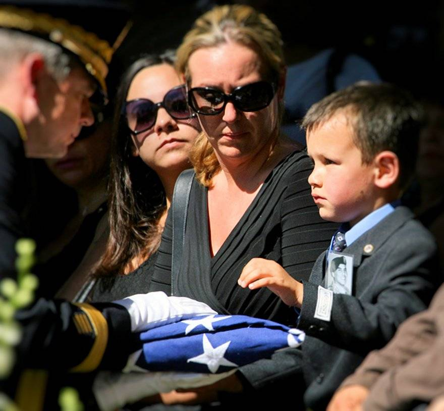 MacAidan Gallegos, 5, receives a flag from Brigadier General Sean MacFarland as Amanda Doyle, MacAidan's mother, watches during the funeral services for Army Sgt. Justin Gallegos at Evergreen Cemetery in Tucson, Ariz. Thursday, Oct. 15, 2009. AP Photo/Ari