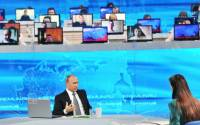 Russian President Vladimir Putin, foreground, answers questions from the public during the annual Direct Line with Vladimir Putin special broadcast live on Russian television and radio