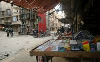 Civilians walk near goods displayed for sale in Aleppo's rebel-controlled Bustan al-Qasr neighbourhood