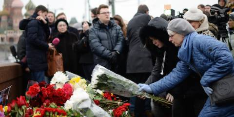 People bring flowers at a murder scene of politician Boris Nemtsov, who was shot dead on Moscow's Moskvoretsky bridge in the early hours of February 28, 2015 | Photo: RIA Novosti