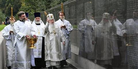 Priests bless the memorial to the victims of the Great Terror at Butovo