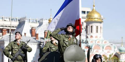 A Russian serviceman aboard an armoured personnel carrier salutes next to the blue-white-red tricolour flag of Crimea, during the Victory Day parade in Moscow's Red Square May 9, 2014