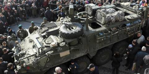 """People gather around an U.S. Army 2nd Cavalry Regiment """"Stryker"""" armored fighting vehicle in Bialystok, Poland, which is a part of the U.S. military """"Dragoon Ride"""" operation. March 24, 2015 