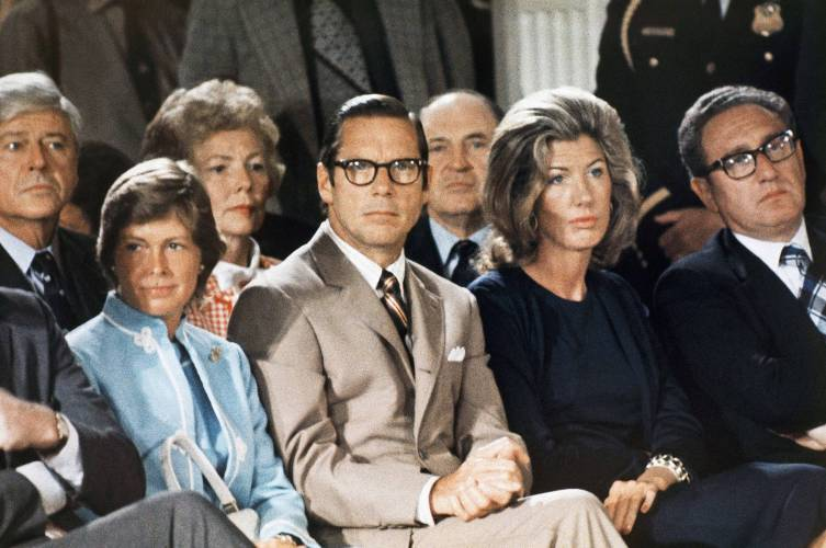 Treasury Secretary William Simon, left, sits with Nancy Kissinger and Secretary of State Henry Kissinger as they listen to former President Nixon talk to his staff prior to leaving the White House for the last time, August 9, 1974