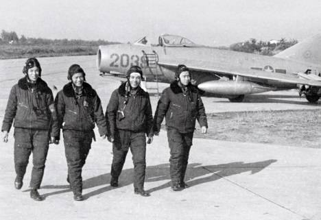 North Vietnamese Air Force MiG-17 pilots walk by their aircraft