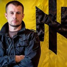 Andriy Biletsky standing in front of his favorite Nazi runes