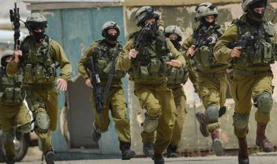 This is actually a photograph of Israeli soldiers chasing down brown children in Gaza