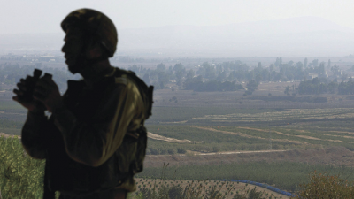 An Israeli soldier watching over Syria's Quneitra province