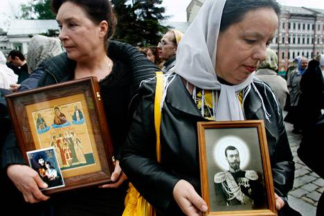 <figcaption>Women hold icons depicting the last Russian Czar Nicholas II</figcaption>