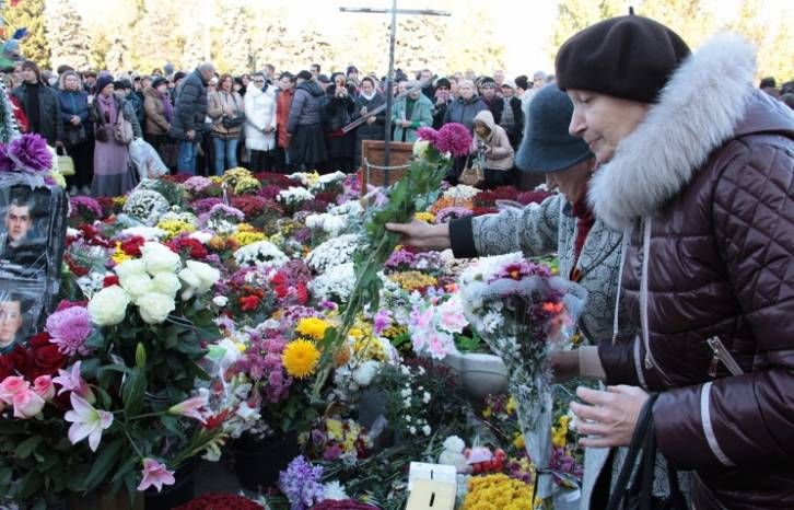 <figcaption>People lay flowers during a rally to remember federalization supporters who died on 2 May 2014 in Odessa</figcaption>