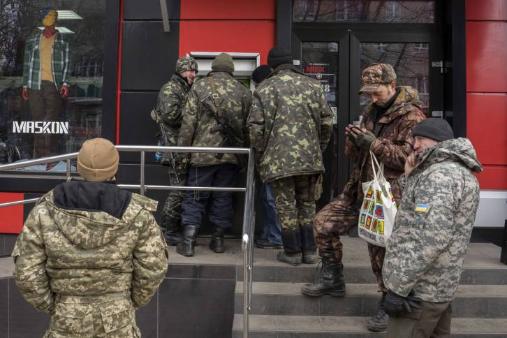 <figcaption>Ukrainian troops queue to withdraw hryvnia cash from an automated teller machine in Artemivsk, Ukraine, on Feb. 20, 2015 | Photo: Vincent Mundy, Bloomberg</figcaption>