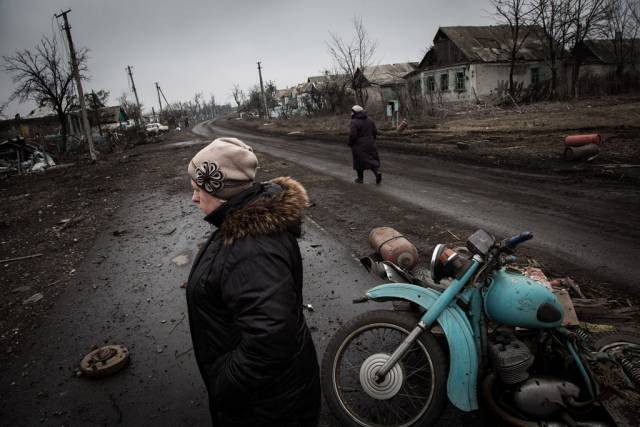 <figcaption>Residents walk along the main road of Nikishino village in eastern Ukraine. Photo: UNHCR Andrew McConnell</figcaption>
