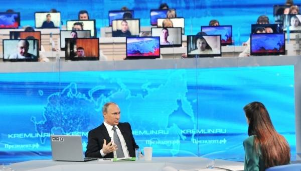 <figcaption>Russian President Vladimir Putin, foreground, answers questions from the public during the annual Direct Line with Vladimir Putin special broadcast live on Russian television and radio</figcaption>