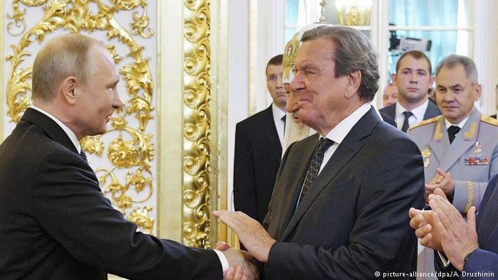<figcaption>Putin being congratulated by the former Chancellor of Germany, Gerhard Schroeder</figcaption>