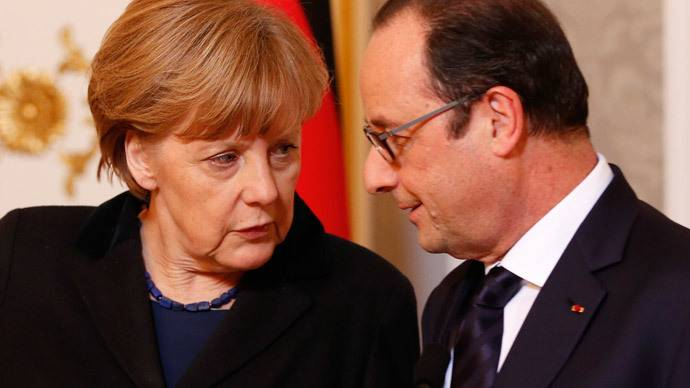 <figcaption>Germany's Chancellor Angela Merkel (L) talks to France's President Francois Hollande during a meeting with the media after peace talks on resolving the Ukrainian crisis in Minsk, February 12, 2015 | Grigory Dukor, Reuters</figcaption>