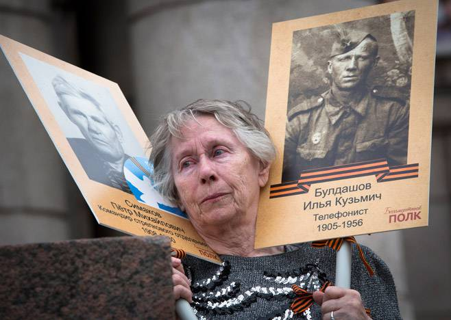 <figcaption>A woman holds portraits of her father and father-in-law</figcaption>