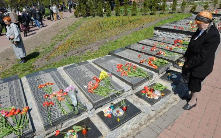 <figcaption>An elderly woman pays her respects to the victims of the Chernobyl nuclear disaster at a memorial in Kiev on April 26, 2015</figcaption>