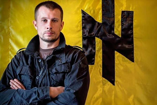 <figcaption>Andriy Biletsky standing in front of his favorite Nazi runes</figcaption>