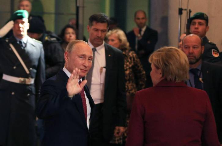 <figcaption>Vladimir Putin waves as he arrives with Angela Merkel during a four-way leaders' summit in Berlin on Oct. 19. </figcaption>