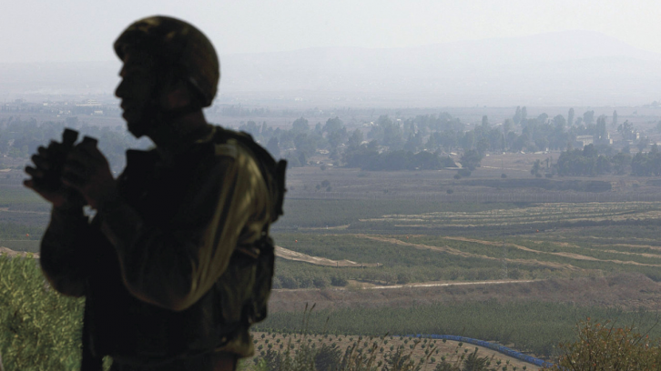 <figcaption>An Israeli soldier watching over Syria's Quneitra province</figcaption>