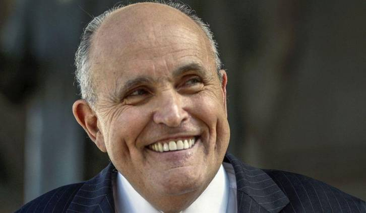 <figcaption>Rudy Giuliani is grinning like the Cheshire cat. His standard smile.</figcaption>