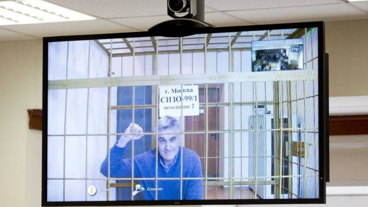 <figcaption>Michael Calvey appears on a television screen via a video-link during a hearing in Moscow on Feb. 28.</figcaption>