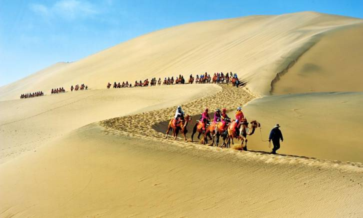<figcaption>Tourists ride on the back of camels with a guide in the desert of Soughing Dunes (Mingshashan), a landmark on the famous Silk Road in China. Image: iStock</figcaption>