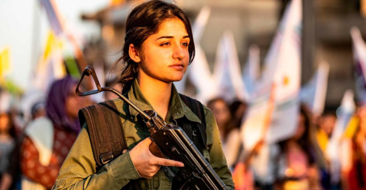 <figcaption>But... if US troops withdraw, evil Turkish Sultan Erdogan will kill this homely Kurdish girl pretending to hold a rifle. Sad!</figcaption>