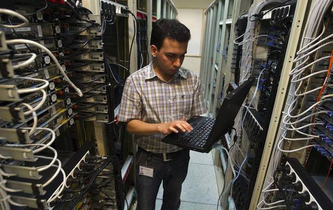 <figcaption>A computer engineer checks equipment at an internet service provider in Tehran, Iran.</figcaption>
