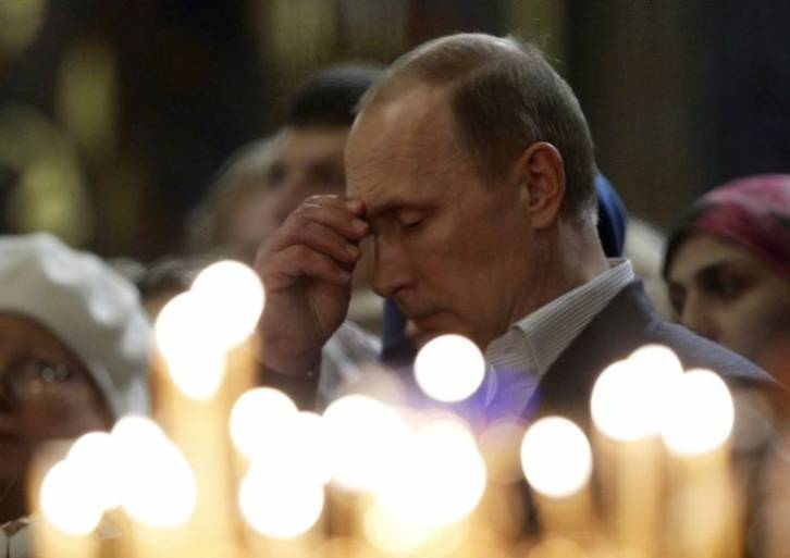 <figcaption>Russia's President Vladimir Putin makes the sign of the cross as he attends the Orthodox Christmas service at the Holy Face of Christ the Savior Church in the city of Sochi, Russia, late 06 January 2014.</figcaption>