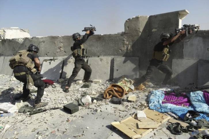 """<figcaption>Iraqi """"Special Operations Forces"""" in action.  Actually this shot is from 2014, but guys firing blind over a wall gives you a sense of the quality of Iraq's so-called army.</figcaption>"""