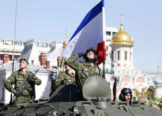 <figcaption>A Russian serviceman aboard an armoured personnel carrier salutes next to the blue-white-red tricolour flag of Crimea, during the Victory Day parade in Moscow's Red Square May 9, 2014</figcaption>