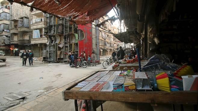 <figcaption>Civilians walk near goods displayed for sale in Aleppo's rebel-controlled Bustan al-Qasr neighbourhood</figcaption>